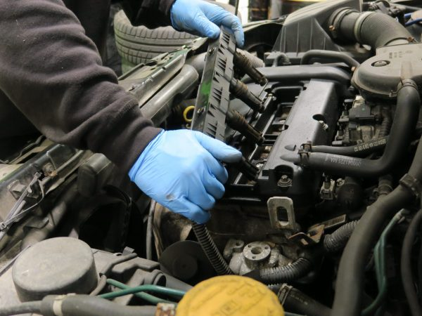 A mechanic begins to strip engine under bonnet